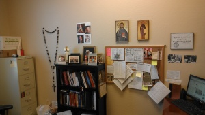 Wall rosary, St. Benedict icons, yes, that's a mini statue of JP2, BW of Chesterton, BW of C.S. Lewis, pictures of my favorite girls and my bulletin board.