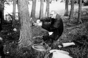 Fr. Karol Wojtyla rocking the sneakers (maybe Chuck Taylors) and eating a pastry.