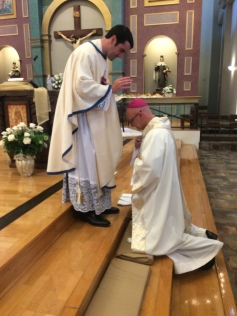 Newly ordained, Fr. Ryan Lee, blessing Bishop James Wall of the Diocese of Gallup.